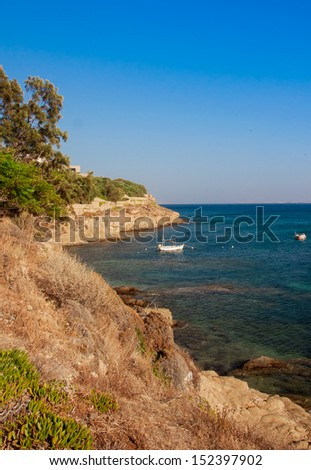 Small fishing boat in the sea off the rocky shore - stock photo