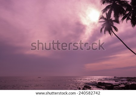 Small fishing boat in tropical ocean landscape with horizon and coconut palms in violet pink color filter. - stock photo