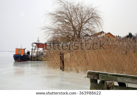 Small fishing boat moored in a small marina on the frozen bay - stock photo