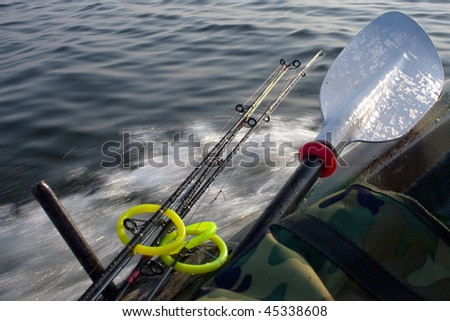 small fishing boat with fishing rods and paddles - stock photo