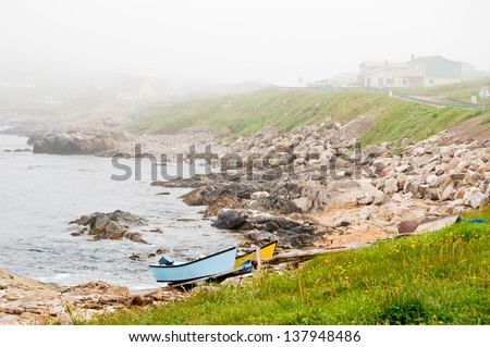 Small fishing boats are pulled up to the rocky coast just outside of St Pierre city. - stock photo
