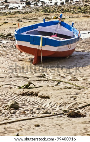 Small fishing boats during low tide. - stock photo