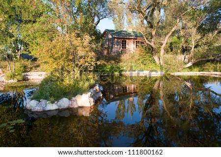 Small fishing house reflecting in the lake by autumn