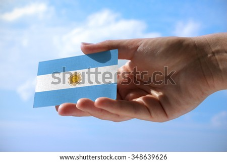 Small flag of Argentina, cumulus clouds in background - stock photo