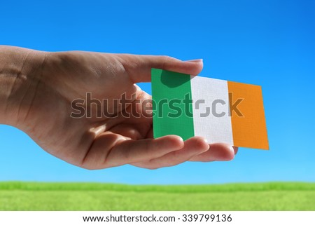 Small flag of Ireland against beautiful landscape with grass - stock photo