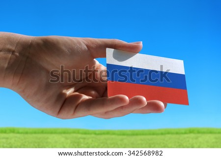 Small flag of Russia against beautiful landscape with grass