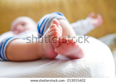 small foot of the sleeping baby in bad. close-up - stock photo