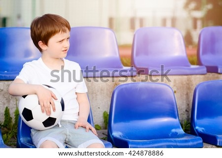Small football fans disappointed after the loss goal by his favorite team - stock photo