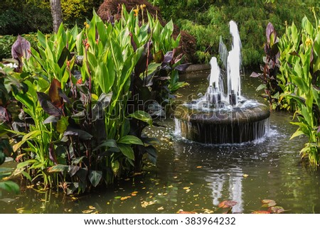Small fountain in quiet pond. Autumn day in the park Butchart. Gardens on Vancouver Island, Canada - stock photo