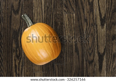 Small fresh bright orange pumpkin on weathered dark wooden surface. - stock photo