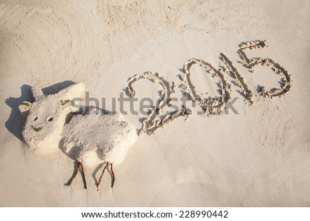Small funny sculpture of the Goat (symbol of 2015 year) and 2015 number on sandy Cyprus beach - stock photo