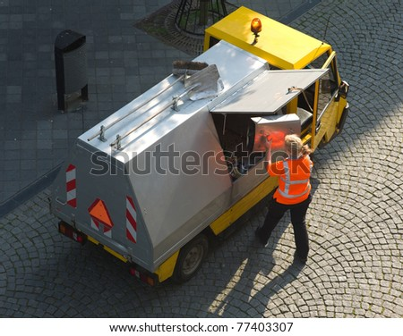 Small garbage truck with female worker - stock photo