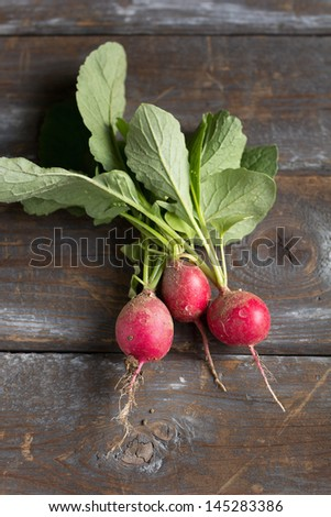 Small garden radish on old wooden background - stock photo