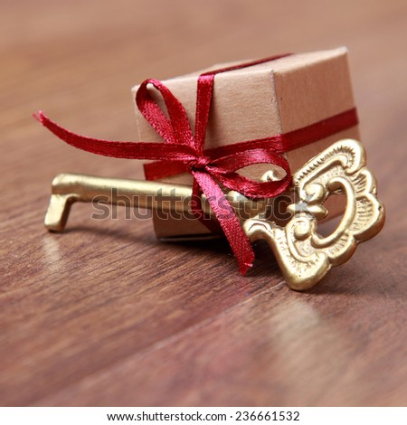 small gift box and vintage key on Holiday theme/Vintage gift box (package) with golden old key over dark brown wooden background. - stock photo