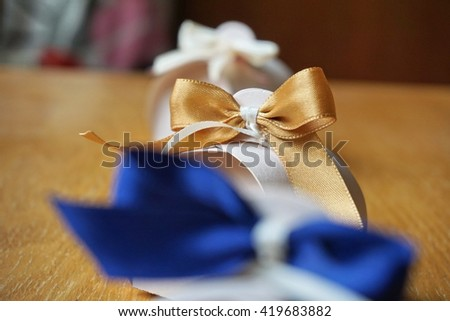 Small gift box made of paper with a colorful ribbon knot atop on a wooden background   - stock photo