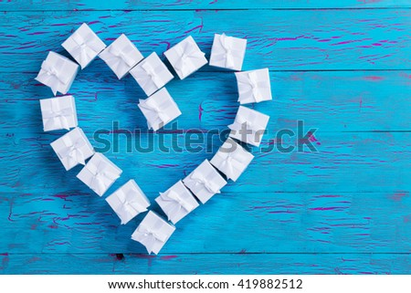 Small gift boxes tied with bows arranged in a heart shape symbolic of love and romance on a rustic blue wood background with crackle paint and copy space for your message to a loved one - stock photo
