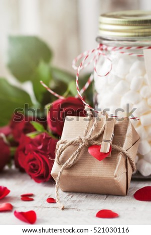 Small gift or present in natural paper with small heart and roses, love or valentine's day concept