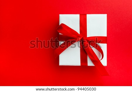 Small gift with red bow on red background. Space for your text. - stock photo