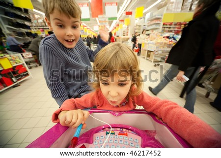 Small girl and boy sit in shopping cart, play new toy and smile