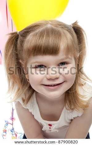 small girl bending over leaning towards camera smiling.