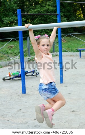 Small girl doing sports exercises in the park