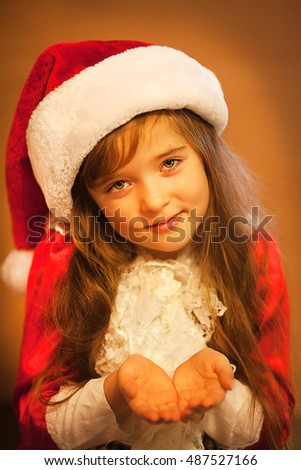 Small girl dressed as santa claus blows snow flakes from palm. Isolated on white background