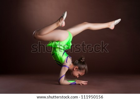small girl gymnast stand on hands - stock photo