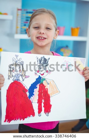Small girl holding a lovely drawing at their desk - stock photo