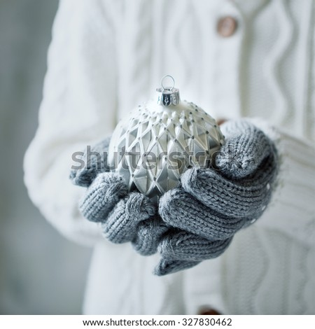 Small girl holding white Christmas ball (close up) - stock photo