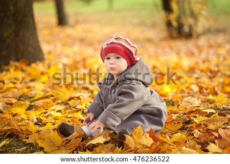 Small girl in autumn park sitting on vibrant leaves