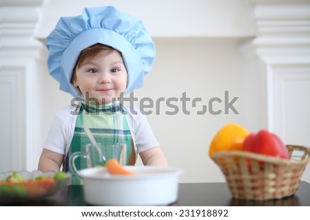 Small girl in kitchen apron and cap play at table with vegetables