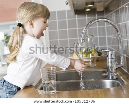 Small Girl in the kitchen drinking water - stock photo