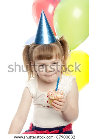 small girl is licking her lips over the yummy cup cake in her hand