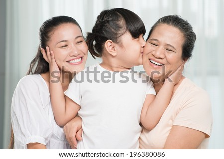 Small  girl kissing her grandmother and bonding her mother - stock photo