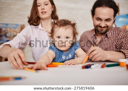 Small girl looking at camera on background of her parents
