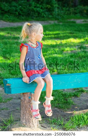 Small girl on bench in summer blossoming garden. - stock photo