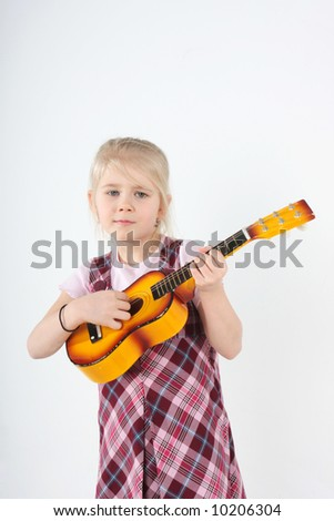 small girl playing a toy guitar