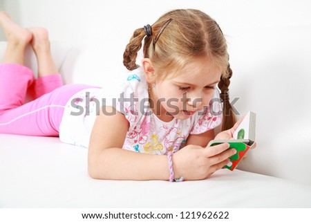 Small girl relaxing and reading
