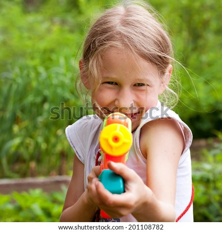 small girl shooting from funny toy water gun - stock photo