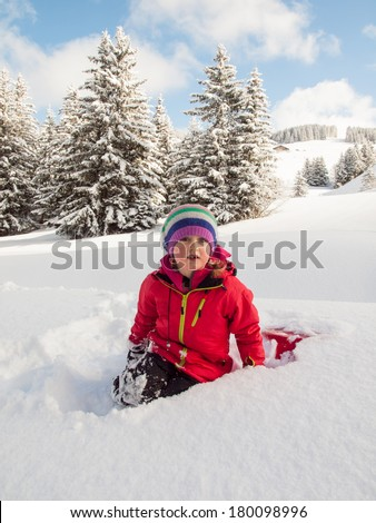 small girl sitting in deep snow with sledge in hand and wooded winter  mountain landscape behind