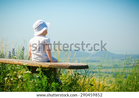 Small girl wearing a hat is sitting on a bench on the top of the hill and watching the landscape - stock photo