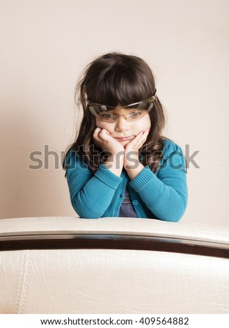 Small girl wearing scientific glasses relaxing on a handle of Sofa inside studio
