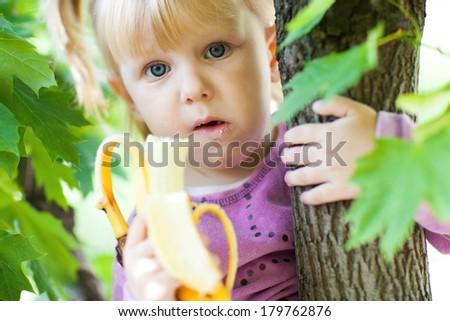 small girl with banana - stock photo