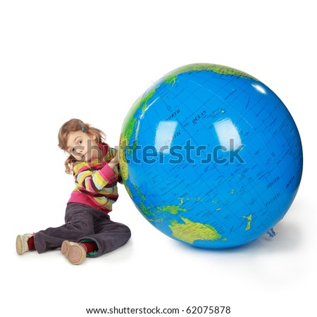small girl with enormous globe select place, where she will live when she will grow - stock photo