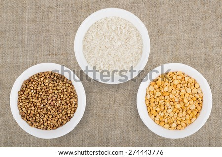 Small glass bowls with dry rice, buckwheat and peas shelled on burlap - stock photo