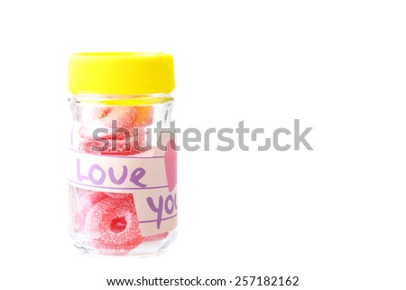 Small glass jar with the words I love you filled with ring candies - stock photo