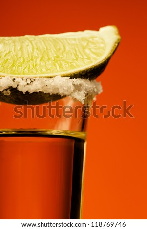 Small glass of tequila with lime and salt on red background - stock photo