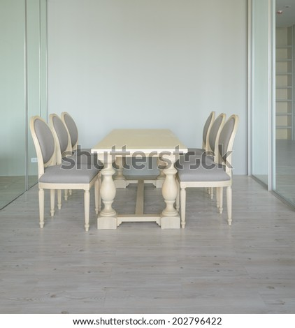 Small glass room with a table and fabric chairs