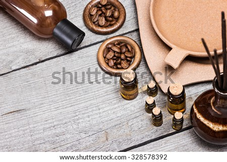 Small glass vials of aromatic essential oils next to crock with incense sticks, bamboo plate with water and coffee beans, massage oil bottle on old wooden planks. Grey and brown colors. Copy space - stock photo