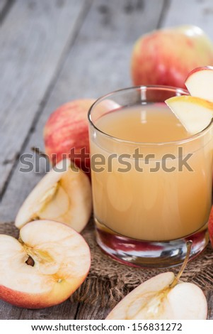 Small Glass with fresh Apple Juice on wooden background